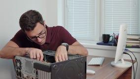 Junge Berufsarbeitskraft, die versucht, einen Computer im Büro unter Verwendung eines Schraubenziehers zu reparieren und Computer stock video footage