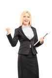 Junge Berufsfrau, die ein Klemmbrett hält und happ gestikuliert Stockbild