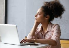 Junge berufstätige Frau, die heraus Fenster schaut Lizenzfreie Stockbilder