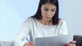 Junge beschäftigte Frau, die Bericht vorbereitet und die Anmerkungen sitzen im Café macht lizenzfreie stockfotos