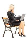 Junge beschäftigte Geschäftsfrau, die auf einer Bank sitzt und an einem Schoss arbeitet Stockfotografie
