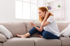 Junge besorgte Frau mit neuem Schwangerschaftstest Stockbild