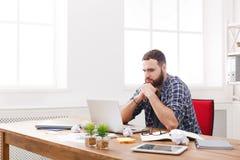 Junge betonten IT-Manager mit Laptop im modernen weißen Büro Stockfotografie