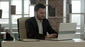 Junge betonter Geschäftsmann, der an Computer arbeitet stock footage