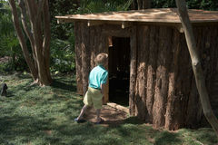 Junge betritt ein Spielhaus an einem Garten im Freien Stockfotos