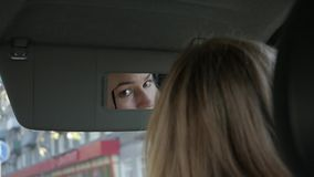 Junge bezaubernde Frau malt Augenbrauen in einem Auto, das zum Rückspiegel schaut Langsame Bewegung stock video
