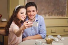 Junge bezauberten die Paare, die an einem Tisch in einem Café sitzen und selfie machen Lizenzfreie Stockfotografie