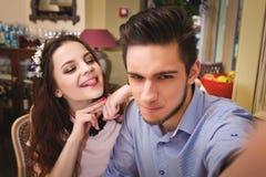 Junge bezauberten die Paare, die an einem Tisch in einem Café sitzen und selfie machen Lizenzfreie Stockfotos