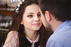 Junge bezauberten die Paare, die an einem Tisch in einem Café sitzen und zu gehen Stockfoto