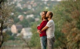 Junge bezaubertes Paar steht und Umarmungen auf Rest im Wald Lizenzfreie Stockfotografie