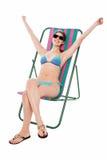 Junge Bikinifrau, die auf deckchair sich entspannt Lizenzfreie Stockbilder