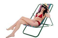 Junge Bikinifrau, die auf deckchair sich entspannt Lizenzfreies Stockfoto