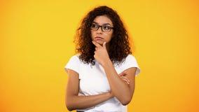 Junge biracial Frau in den Brillen denkend an Entscheidung, gelber Hintergrund lizenzfreies stockbild