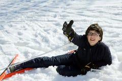 Junge bittet um Hilfe nach dem Fall mit Skis Lizenzfreies Stockfoto