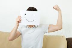 Junge blinzelt und junger Mann der Erhöhungsfaust annonciert erfolgreichen Modus Stockbild