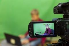 Junge Blogger notiert Video auf einem grünen Hintergrund Stockbilder