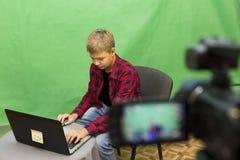 Junge Blogger notiert Video auf einem grünen Hintergrund Stockfotos
