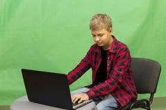 Junge Blogger notiert Video auf einem grünen Hintergrund Lizenzfreie Stockbilder