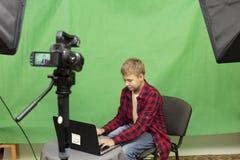 Junge Blogger notiert Video auf einem grünen Hintergrund Stockbild