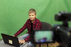 Junge Blogger notiert Video auf einem grünen Hintergrund Lizenzfreie Stockfotos