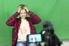 Junge Blogger notiert Video auf einem grünen Hintergrund Stockfotografie