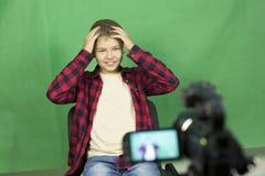 Junge Blogger notiert Video auf einem grünen Hintergrund Stockfoto