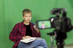 Junge Blogger notiert Video auf einem grünen Hintergrund Lizenzfreies Stockfoto