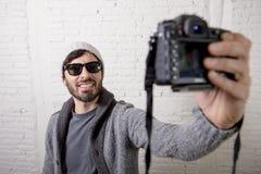 Junge Bloggermannhippie-Art, die Fotokameraschießen selfie Video und Foto hält Stockbild