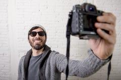 Junge Bloggermannhippie-Art, die Fotokameraschießen selfie Video und Foto hält Lizenzfreies Stockfoto