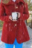 Junge blond-haarige Frau im roten Mantel, der nette PinguinKaffeetasse draußen im Schnee hält Stockfotos