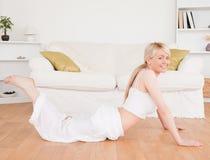 Junge blond-haired Frau, die Eignungübungen tut Lizenzfreie Stockfotografie