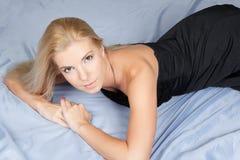 Junge blonde Art und Weisefrau, die im Studio liegt Lizenzfreie Stockfotografie