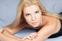 Junge blonde Art und Weisefrau, die im Studio liegt Lizenzfreie Stockfotos