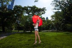 Junge blonde athletische Frau, die einen roten Regenschirm hält Stockfoto