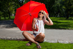 Junge blonde athletische Frau, die einen roten Regenschirm hält Lizenzfreies Stockfoto
