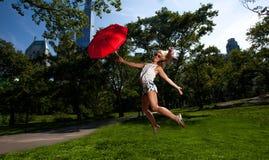 Junge blonde athletische Frau, die einen roten Regenschirm hält Lizenzfreie Stockbilder