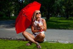 Junge blonde athletische Frau, die einen roten Regenschirm hält Stockfotografie