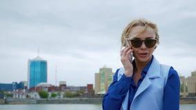 Junge blonde attraktive Frau, die in den Park durch den Fluss geht und am Handy spricht Blaues Hemd, Anzug stock video