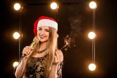 Junge blonde attraktive Frau im roten Hut des neuen Jahres Stockfotografie