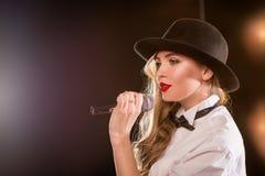 Junge blonde attraktive Frau im weißen Hemd, schwarzer Hut Lizenzfreie Stockfotos