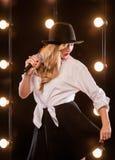 Junge blonde attraktive Frau im weißen Hemd, schwarzer Hut Stockfoto