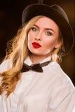 Junge blonde attraktive Frau im weißen Hemd, schwarzer Hut Stockbilder