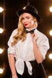 Junge blonde attraktive Frau im weißen Hemd, schwarzer Hut Lizenzfreie Stockfotografie