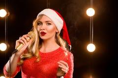 Junge blonde attraktive Frau mit Mikrofon und Wunderkerze auf Stadium Stockfotografie