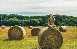 Junge blonde auf Heuschober sitzende und lächelnde Dame, Ungarn Stockbild