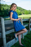 Junge blonde Aufstellung auf dem Sommergebiet nahe einem Zaun Lizenzfreie Stockfotos