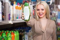 Junge blonde Aufstellung mit Flasche Shampoo Lizenzfreie Stockfotos