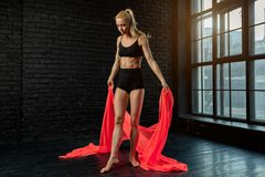 Junge blonde Ballerina in den Sportkleidungsunterwäschetänzen und -sprüngen in einem Studio mit schwarzem Ziegelstein auf dem Hin stockbilder