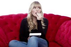 Junge blonde behaarte Mädchengeschmackschokolade auf rotem Sofa vor Lizenzfreie Stockfotografie
