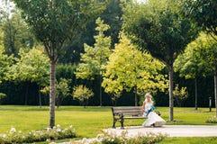 Junge blonde Braut, die auf einer Bank in einem exotischen Park sitzt Stockfoto